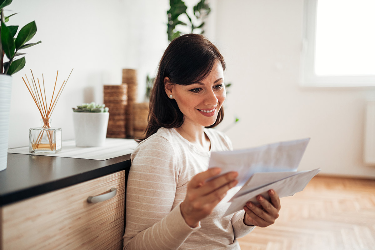 woman looking at mail at cozy home